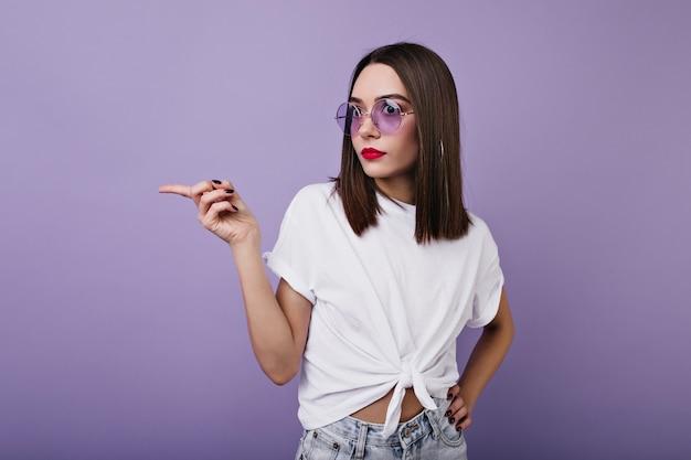 Condizione sottile della ragazza sorpresa. foto interna di donna elegante in maglietta bianca in posa con stupore.