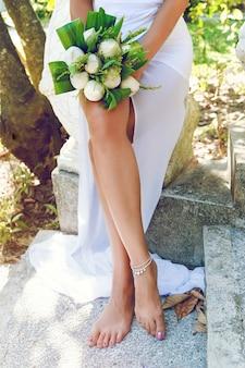 Donna abbronzata sottile che tiene bellissimo bouquet da sposa esotico con fiori di loto bianco, in posa al parco con piani esotici in thailandia.