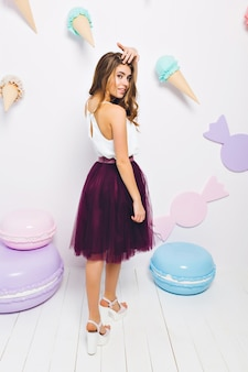 Slim tanned girl in long violet skirt looking over her shoulder posing on theme party and touching hair. full-length portrait of gorgeous young woman standing in light room decorated with candies.