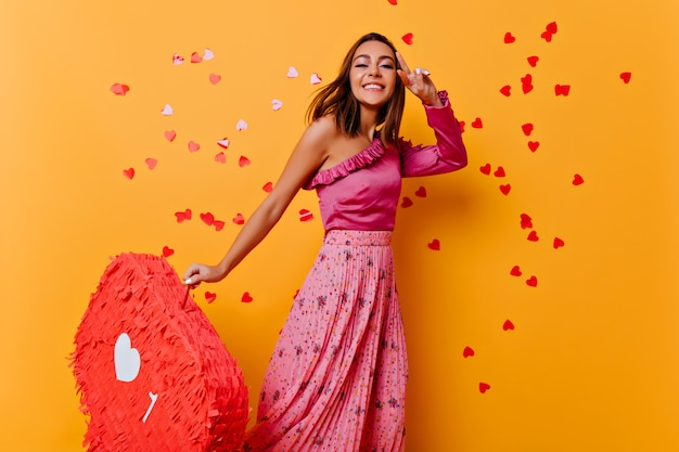 Slim tanned girl in trendy blouse dancing. interested young lady in pink clothes posing on yellow wall.