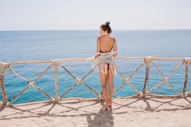 テラスに立って海を見てニットの服装でかわいい髪型のスリムな日焼け少女。夏休みにオーシャンビューを楽しんで、水の前でポーズをとって素晴らしい若い女性