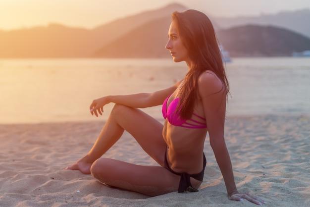 Стройная загорелая модель в бикини позирует на пляже, сидя на песке в свете утра на рассвете с горами и морем в фоновом режиме