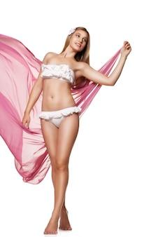 Стройная загорелая сексуальная женщина в белых купальниках в студии изолирована с развевающейся тканью