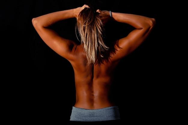 Стройное загорелое сексуальное женское тело на черном фоне