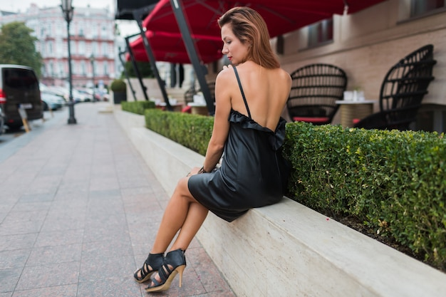 Стройная загорелая женщина в элегантном черном платье и на каблуках с яркими светлыми волосами позирует в старом европейском городе возле роскошного ресторана.