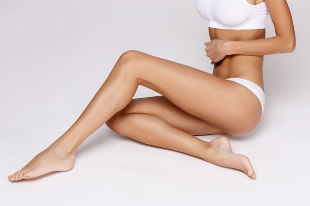 Slim tanned woman's body over gray background