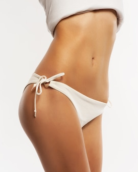 Slim tanned woman's body. isolated over gray background.