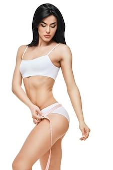 空白で隔離されたスリムな日焼けした女性の体-ウエスト測定。