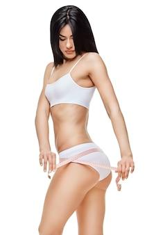 スリムな日焼けした女性の体を隔離-ウエスト測定