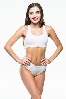 Slim tanned woman's body isolated over white wall.