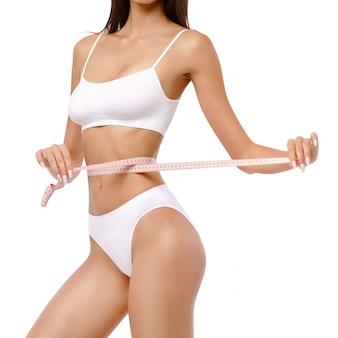 白い壁にスリムな日焼けした女性の体-ウエスト測定