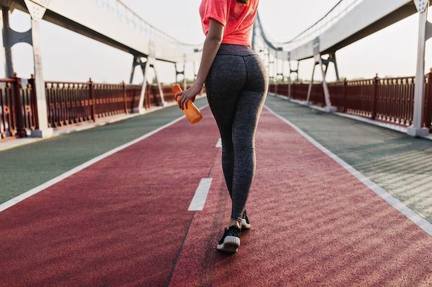 Slim donna abbronzata trascorrere la mattina allo stadio. adorabile ragazza in pantaloni sportivi facendo esercizio nel fine settimana.