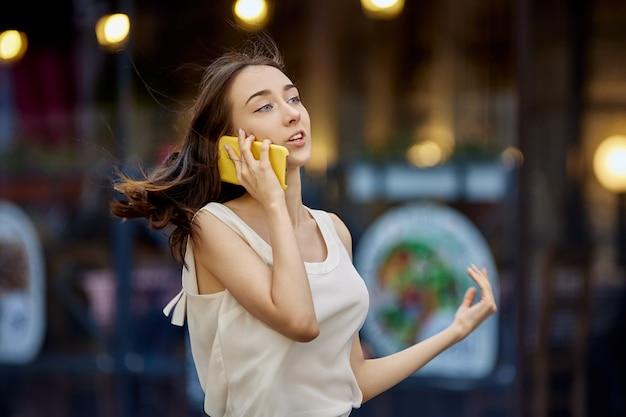 도시 거리에서 스마트폰으로 이야기하는 날씬한 10대 소녀