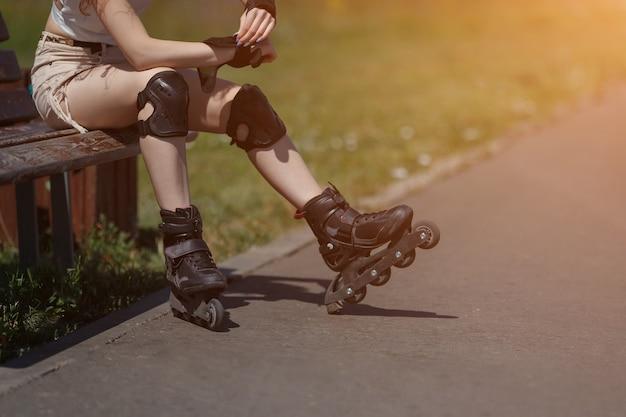 Стройная неизвестная девушка носит наряды для катания на роликах в теплый солнечный день, копировальное пространство. солнечный свет