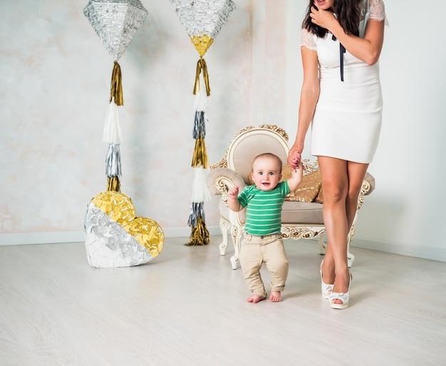 흰 드레스와 하이힐에 슬림 한 정체 불명의 젊은 어머니가 그녀의 잘난 척하는 손으로 걷는다.
