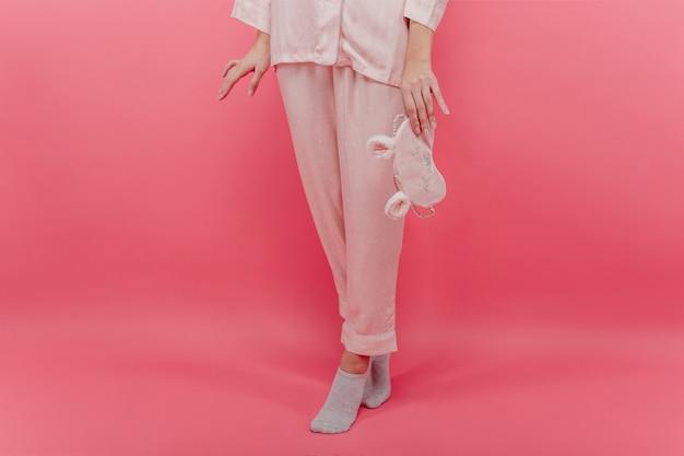 Slim ragazza bianca in calzini carini in piedi sulla punta dei piedi e tenendo la maschera per dormire. foto interna di una bella signora in pigiama di cotone con maschera per gli occhi in posa sul muro rosa.