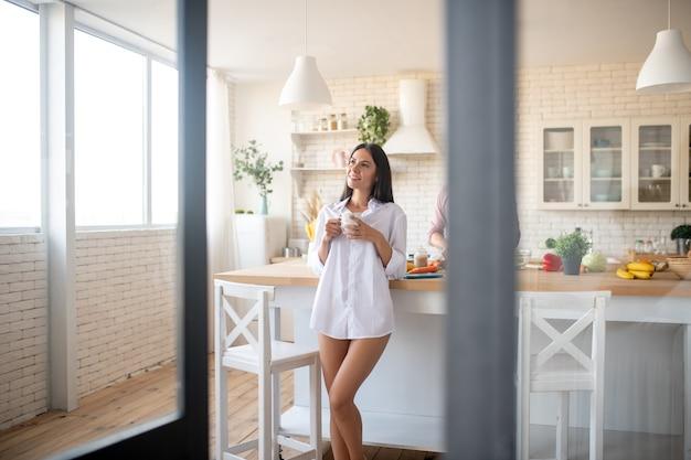 Стройная жена в белой рубашке пьет кофе по утрам