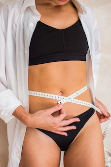 Slim woman in black underwear and white shirt is measuring her thin waist with a tape. weight loss, liposuctoin and fitness concept. vertical.