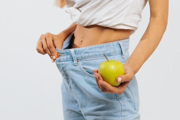 Slim woman in blue jeans holding green apple, wearing oversize jeans. weight loss