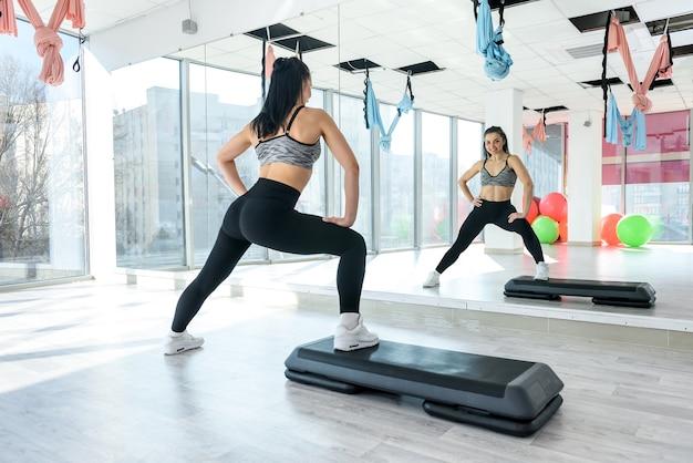 フィットネスジムで腹筋運動ストレッチをしているスリムな女性。健康的な生活様式