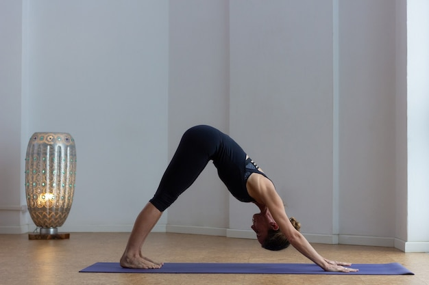Slim woman doing adho mukha svanasana yoga pose in studio. female yogi in downward facing dog asana indoors. staying fit, workout session at home concepts