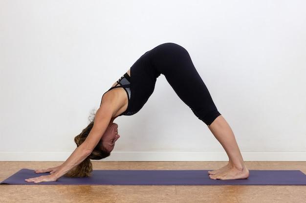 Slim woman doing adho mukha svanasana yoga pose over white background