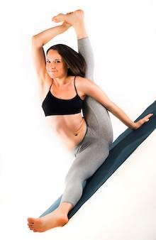 깔개 위에서 고급 자세를 취하는 날씬한 여성