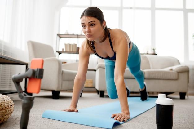 Стройная женщина делает упражнения на коврике, онлайн-обучение на ноутбуке. женский человек в спортивной одежде, спортивная тренировка в интернете, интерьер комнаты