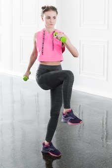 Slim woman doing exercise with green dumbbells
