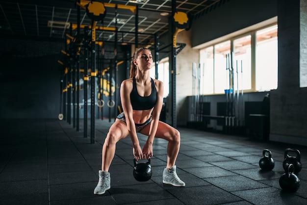 フィットネスクラブで体重を使って運動をしているスリムな女性。ジムでの魅力的な女性アスリートトレーニング