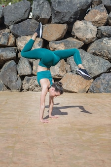 Slim woman doing handstand with splits