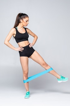 Slim woman doing squats with fitness loop band isolated