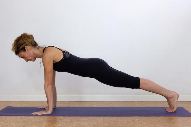 Slim woman doing utthita chaturanga dandasana yoga posture over white background