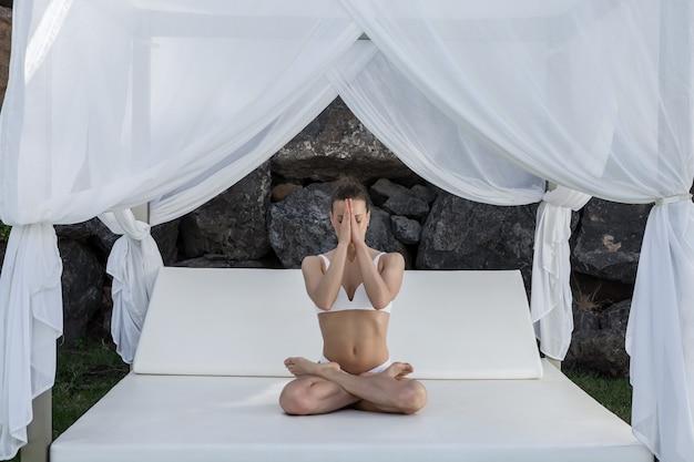 Slim woman doing yoga in padmasana with namaste gesture
