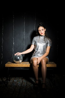 Slim woman in dress with disco ball on bench