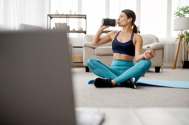 スリムな女性は水を飲み、ラップトップでオンラインフィットネストレーニングを行います。スポーツウェア、インターネットスポーツトレーニング、室内インテリアの女性
