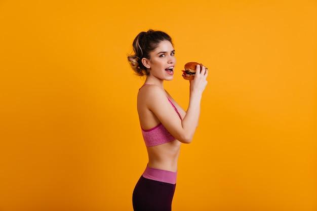 Slim woman eating tasty hamburger
