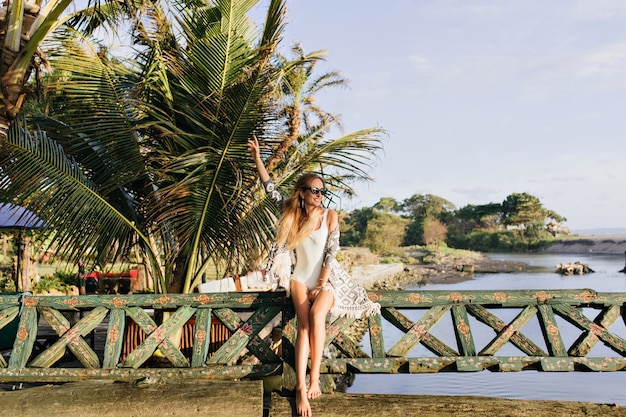 Slim woman enjoying in exotic place. joyful tanned lady standing near palm trees and smiling.