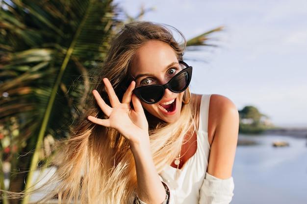 エキゾチックな場所で楽しんでいるスリムな女性。ヤシの木の近くに立って笑っているうれしそうな日焼けした女性。