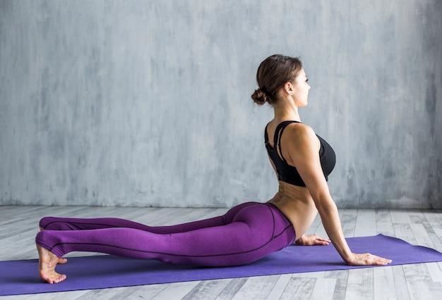 Slim woman executing a cobra stretch