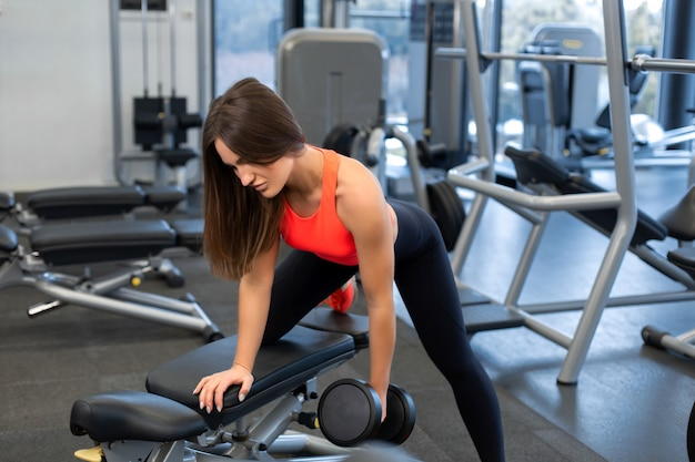 Slim woman exercis with dumbbells on bench at gym