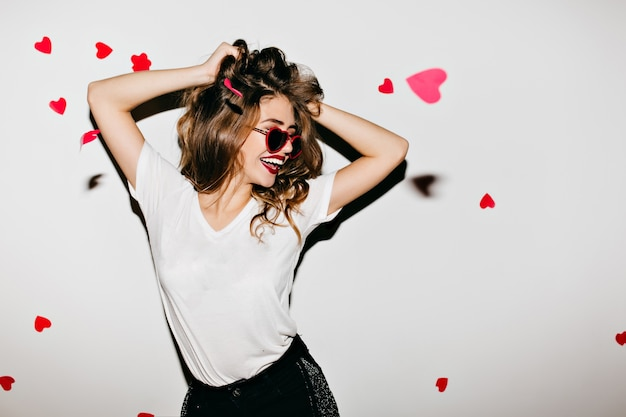 Slim woman in glamorous sunglasses laughing on white wall