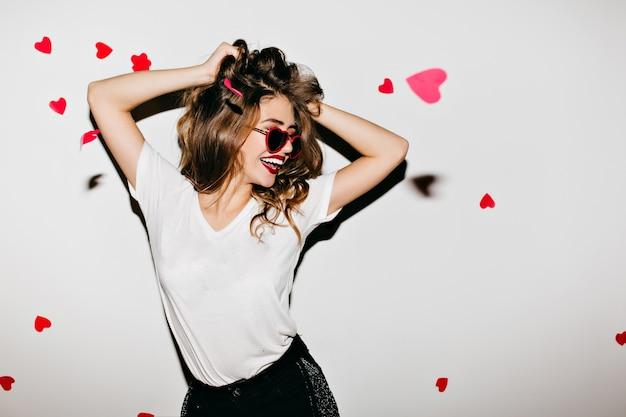 Donna esile in occhiali da sole glamour che ride sul muro bianco