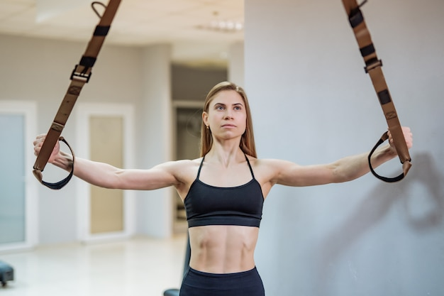 Slim woman in gym training arms with trx fitness strips.