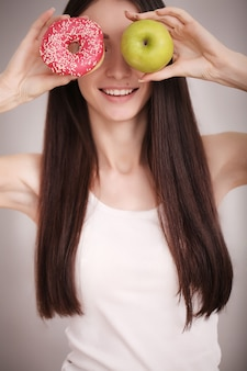 Slim woman hold in hand pink donut and green apple