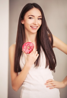 Slim woman hold in hand pink donut