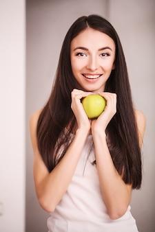 Стройная женщина держит в руке зеленое яблоко