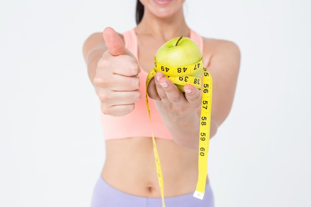 Slim woman holding apple with measuring tape