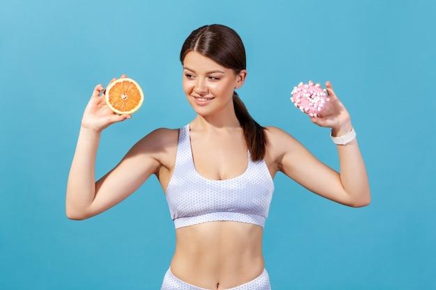 グレープフルーツとドーナツの半分を持って、誘惑でジューシーな甘い果物を見ているスリムな女性