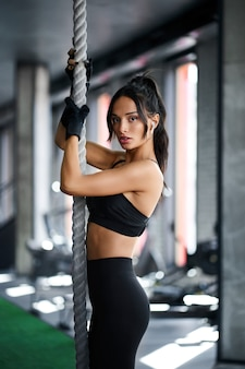 Slim woman holding rope in gym